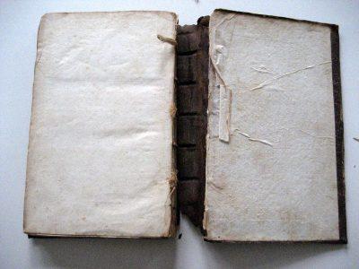 Verbroken verbinding tussen bandzetter en boekblok. Beschadigde schutbladen.