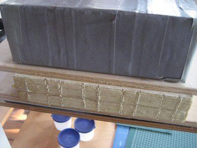 Boekblok ligt te drogen. Gezaagde inkepingen voor draad als extra versteviging.